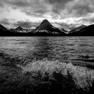 Frigid water laps the shore of a glacier-fed lake while storm clouds appear ominous , Glacier NP, MT