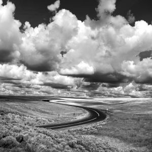 A winding Idaho road is beautifully canopied with cumulus clouds, ID