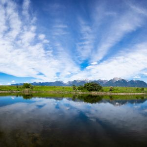 A close reflection of the distant Teton mountain range just off the road, ID
