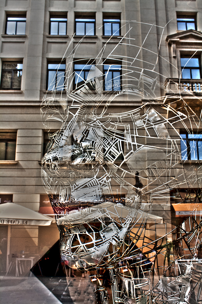 Reflection of building in art gallery window displaying large wire-frame mask, Barcelona, Spain