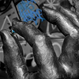 A large statue of a hand holds a small glass sphere as graffitti fills the background, Amsterdam, Netherlands
