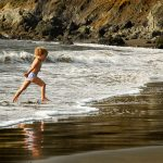 A young child plays tag with the ocean tides, Muir Beach, California