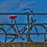 A bicycle parked along the canal bridge railing, Amsterdam, Netherlands