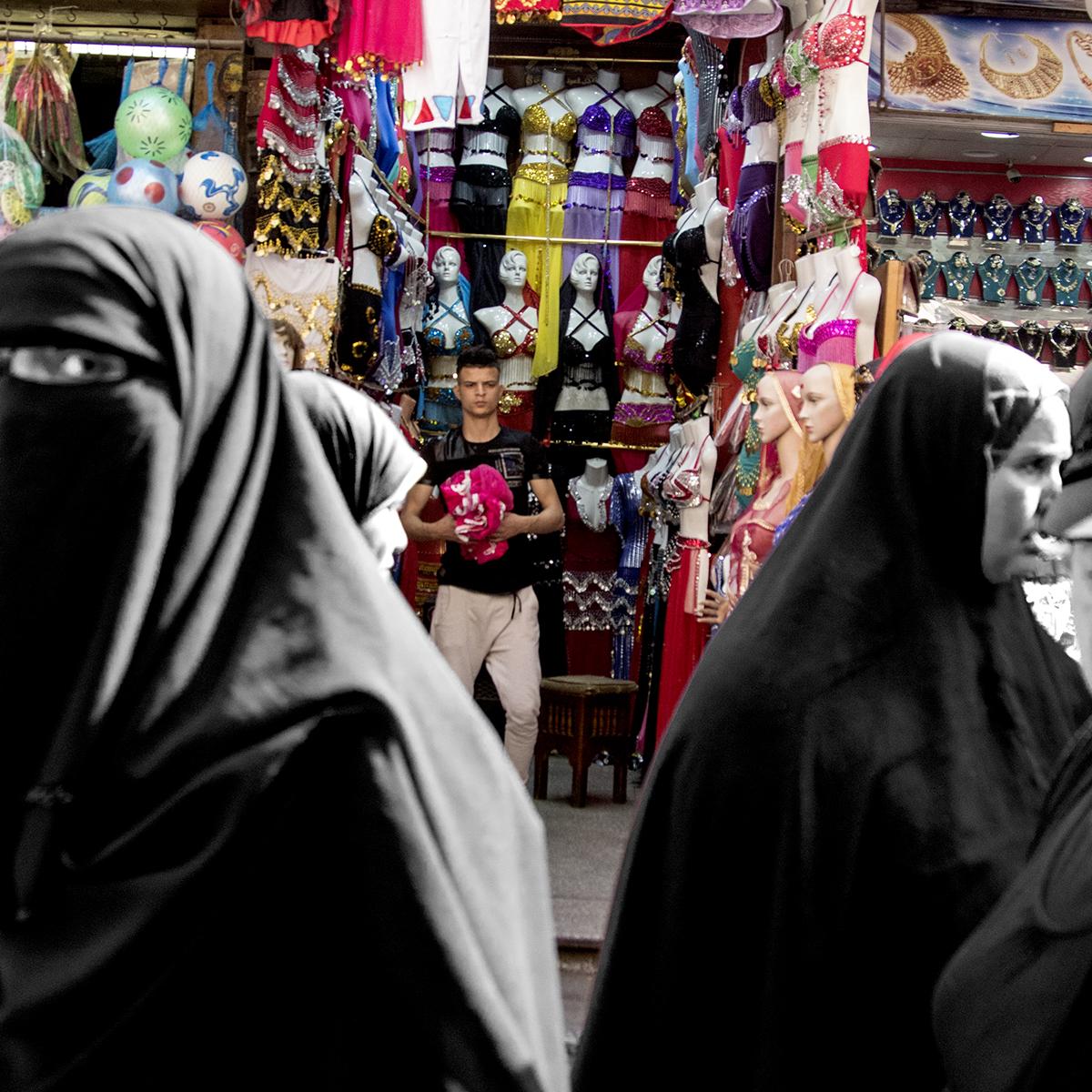Conservative Muslim women pass by a lingerie shop in the Khan Al-Khalili market, Cairo, Egypt