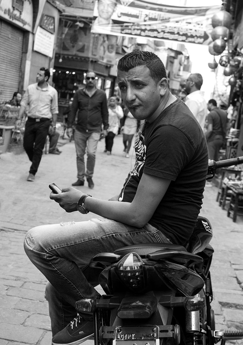 """A young Egyptian man leaning on his cycle does his best """"James Dean"""", Khan Al-Khalili market, Cairo, Egypt"""