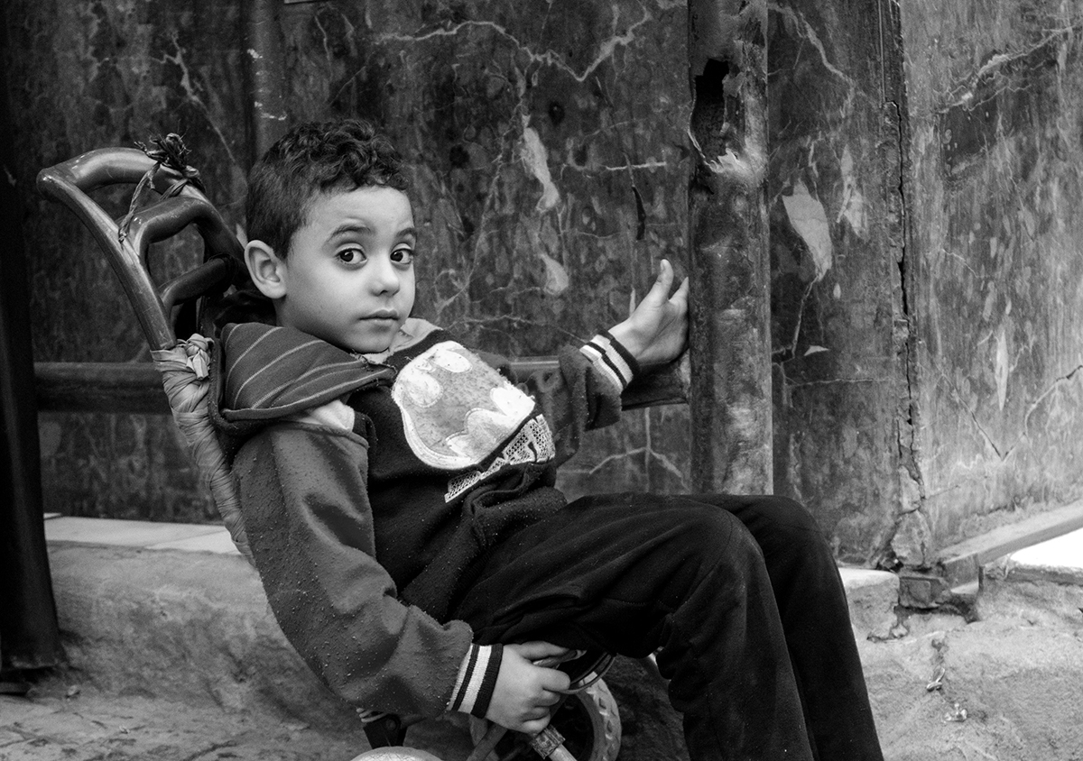 A child in a stroller patiently waits for his mother to finish her shopping, Khan Al Khalili market, Cairo, Egypt