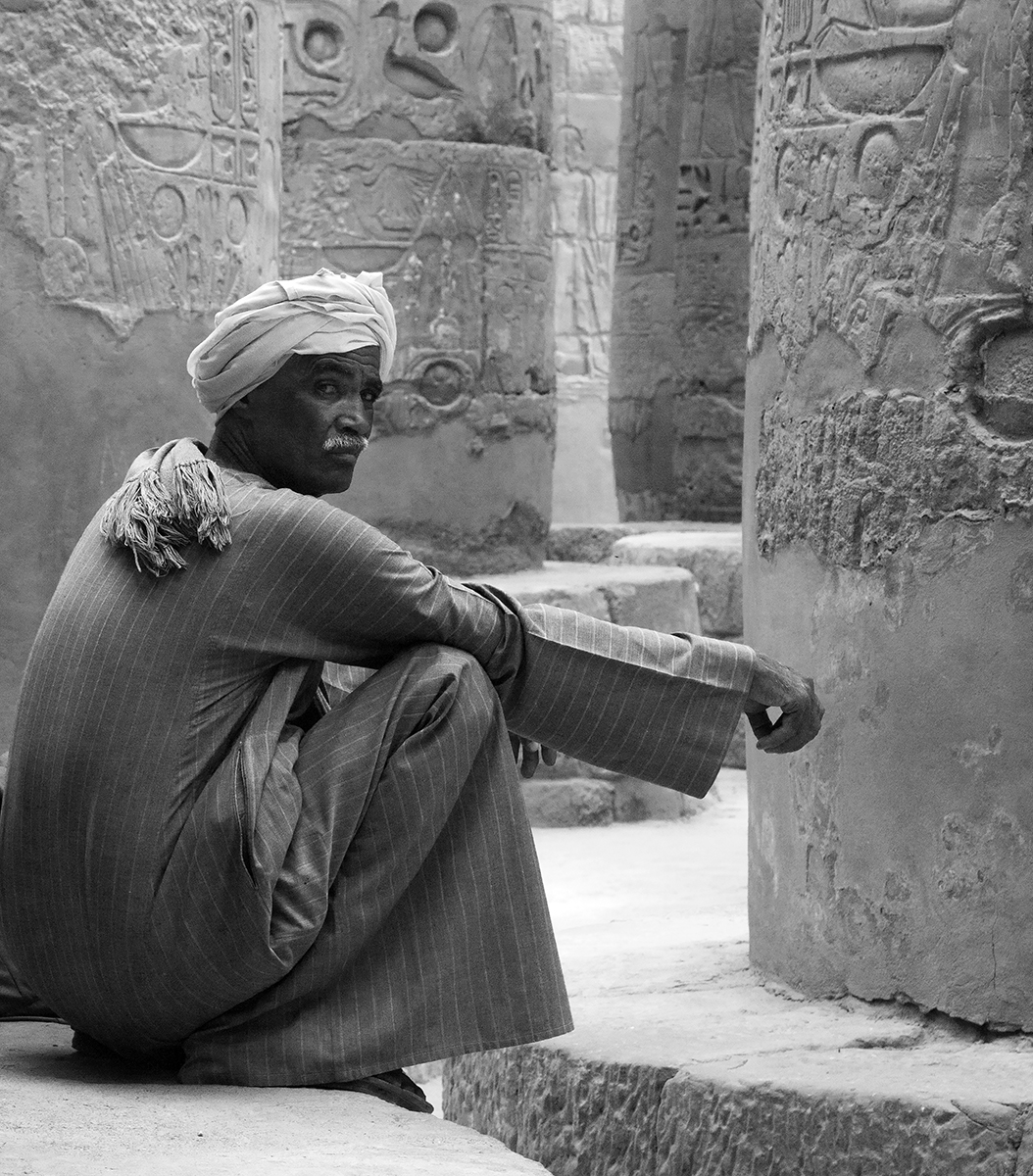 A curator is caught off guard within the forest of massive columns in the Karnak Temple, Luxor, Egypt