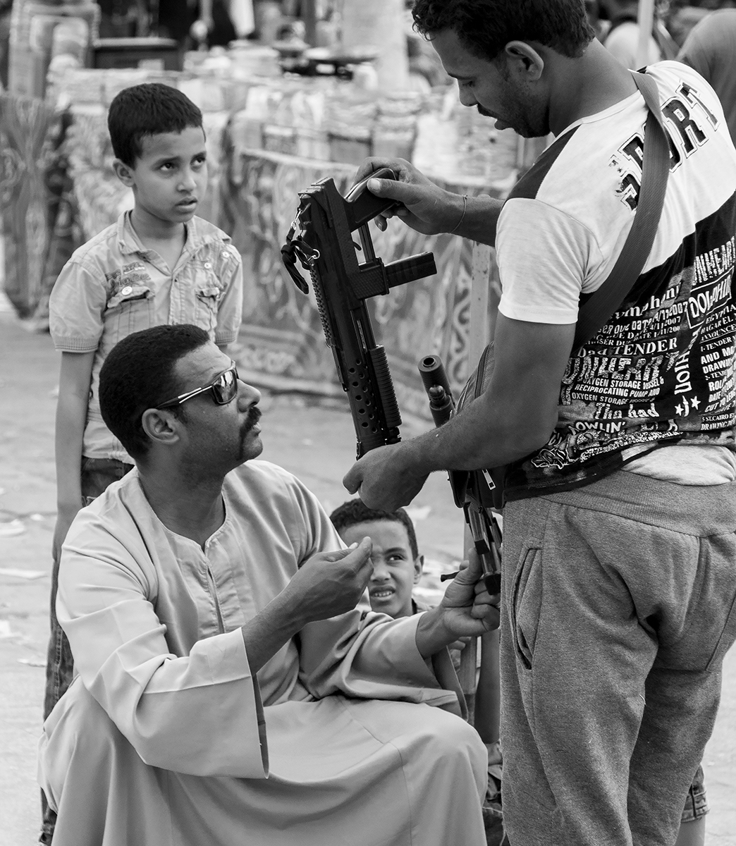 A common business transaction at a local street market, Luxor, Egypt