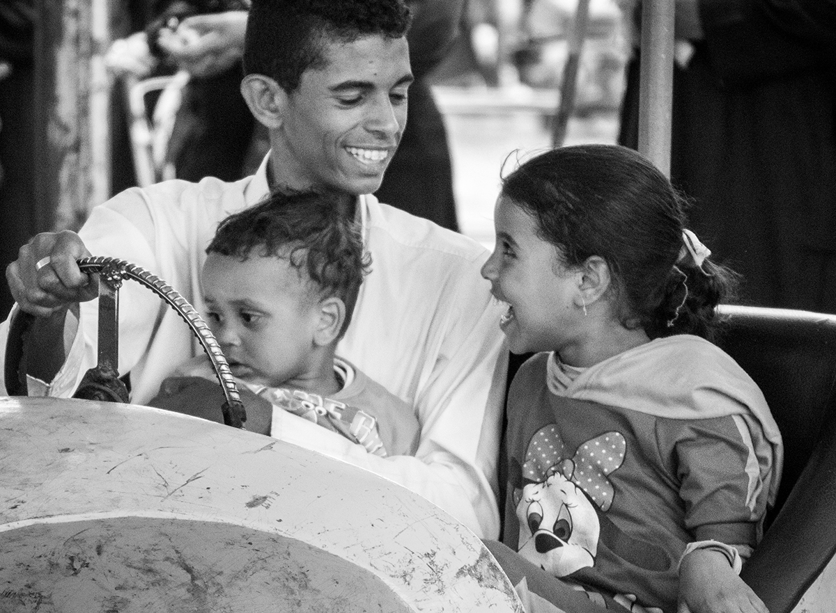 A father and kids enjoy an amusement ride during a local festival, Luxor, Egypt