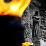 Torch flames in front of ghost statue on medieval city wall, Tallin, Estonia