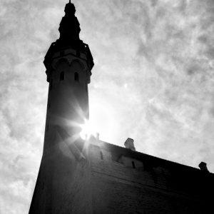 High noon sun behind medieval community hall, Tallin, Estonia