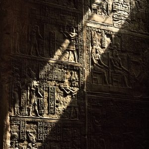 Light streams down along a wall riddled with relief-carved hieroglyphs in the temple of Horus, Edfu, Egypt