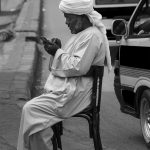 An Egyptian man scans his mobile phone on the island of a very busy street, Edfu, Egypt