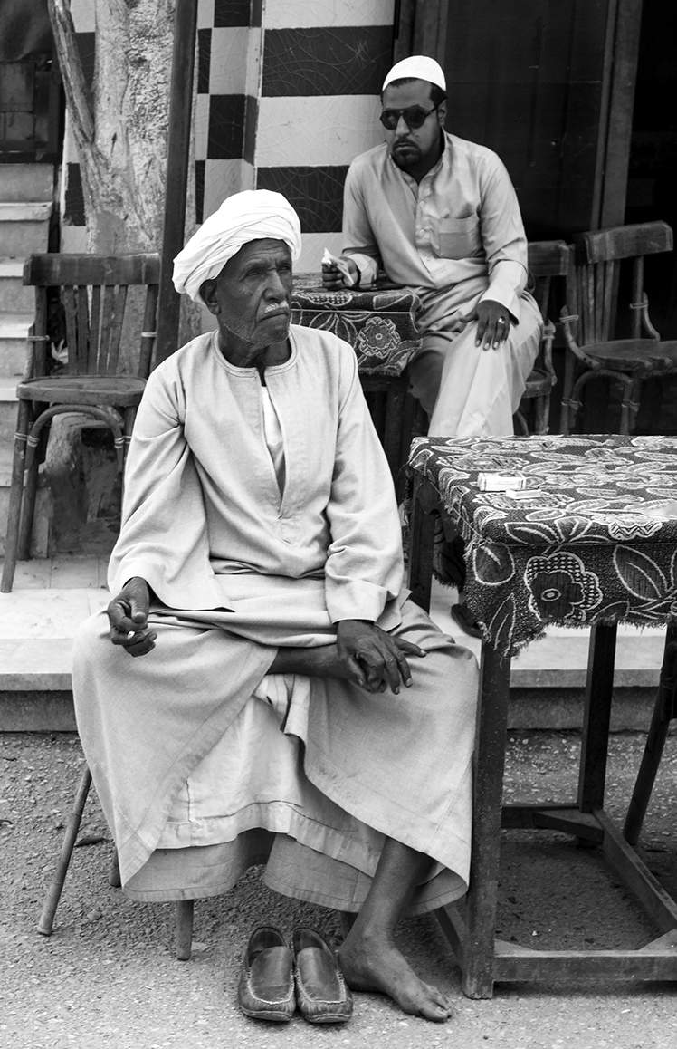 Two Egyptian men rest in the miday sun at a cafe in Edfu, Egypt