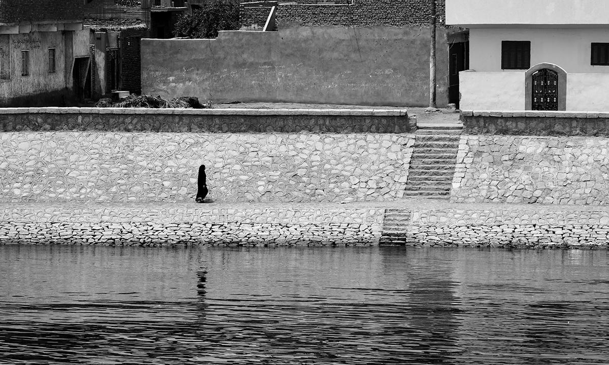 An Egyptian woman walks along the edge of the River Nile, Egypt