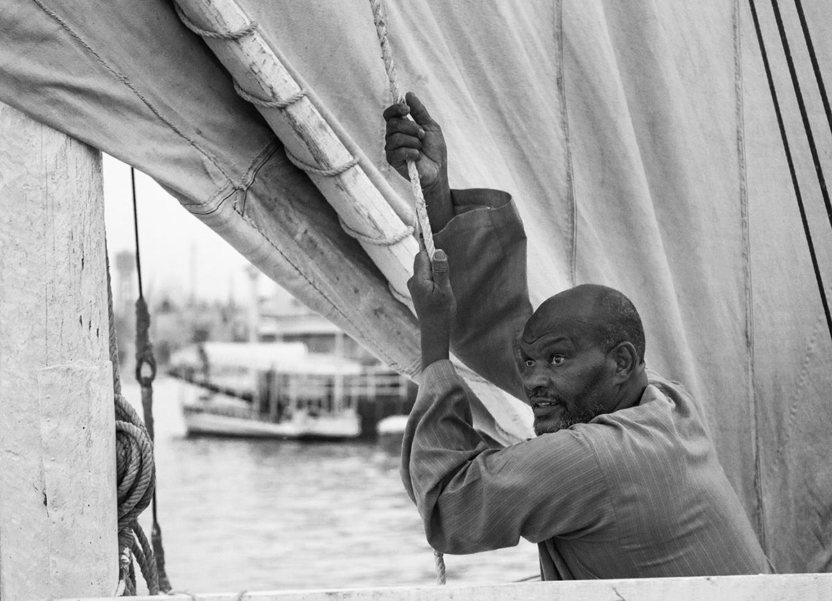 A local felucca boatman hoist the sail during a sunset tour on the Nile, Aswan, Egypt