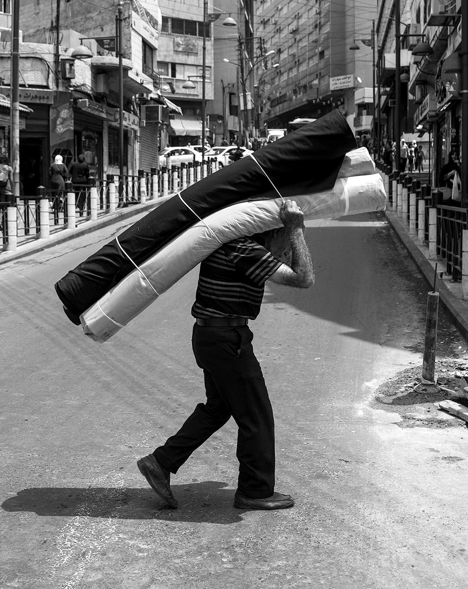An elderly gentlemen carries a load through the streets of Amman, Jordan
