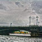 A bridge over the Neva River shot through a rain-slicked cruise boat window, St. Petersburg, Russia