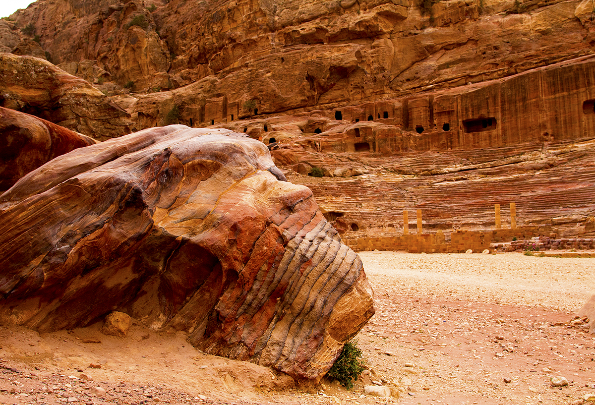 A large sandstone boulder in front of the ancient theater carved from the cliffside, Petra Ruins, Jordan