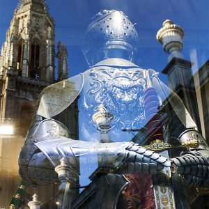 Souvenir armor store front window reflecting cathedral tower