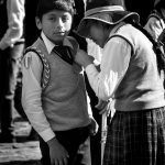 A young local helps her brother prepare for festival parade, Cusco, Peru