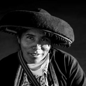 A local Quechuan artisan pears up from her work, Urubamba, Peru