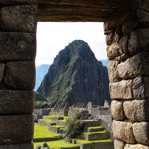 Incan ruin doorway at Machu Picchu with Huayna Picchu in the background, Peru