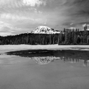 A half frozen pond reflects a beautiful view of Mount Rainier, WA