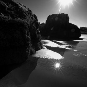 The sun beams reflect off the tidal pools along the Oregon coast